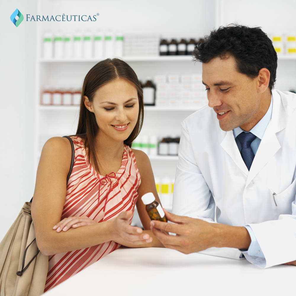 Close-up of pharmacist and patient looking at container of medicine